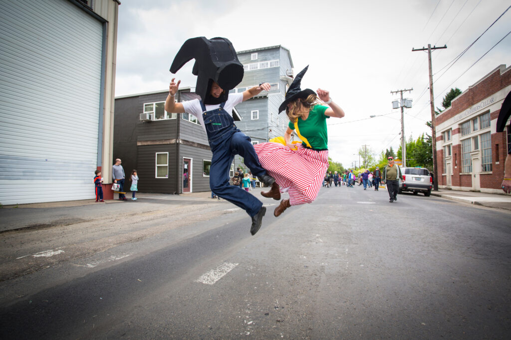 A man dressed as a hammer and a woman dressed as a witch jump and click their heels.  The large historic granary building is in the background.