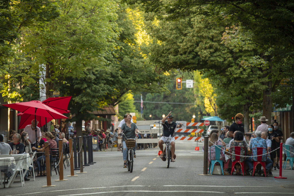 Three cyclists ride down the middle of the street, between two cordoned off sections of outdoor diners.  One cyclist waves.