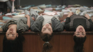 Three preteen girls surrounded by paper airplanes lie down, looking bored.