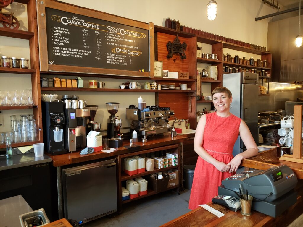 A woman stands and smiles in front of a cash register behind the bar of Community Plate.  The menu and coffee set up are behind her.