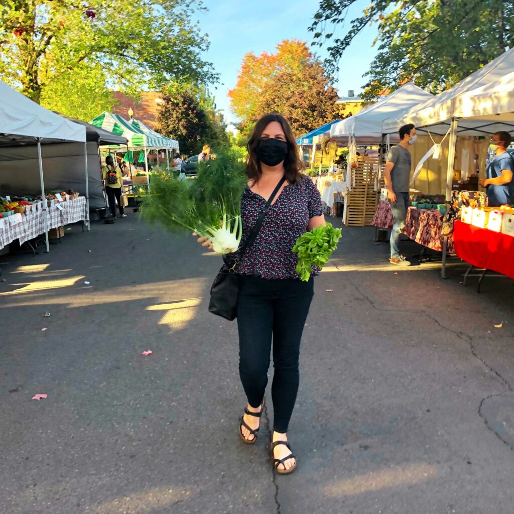 Chef Rebecca strolls through the farmers market with basil and fennel in her hands.
