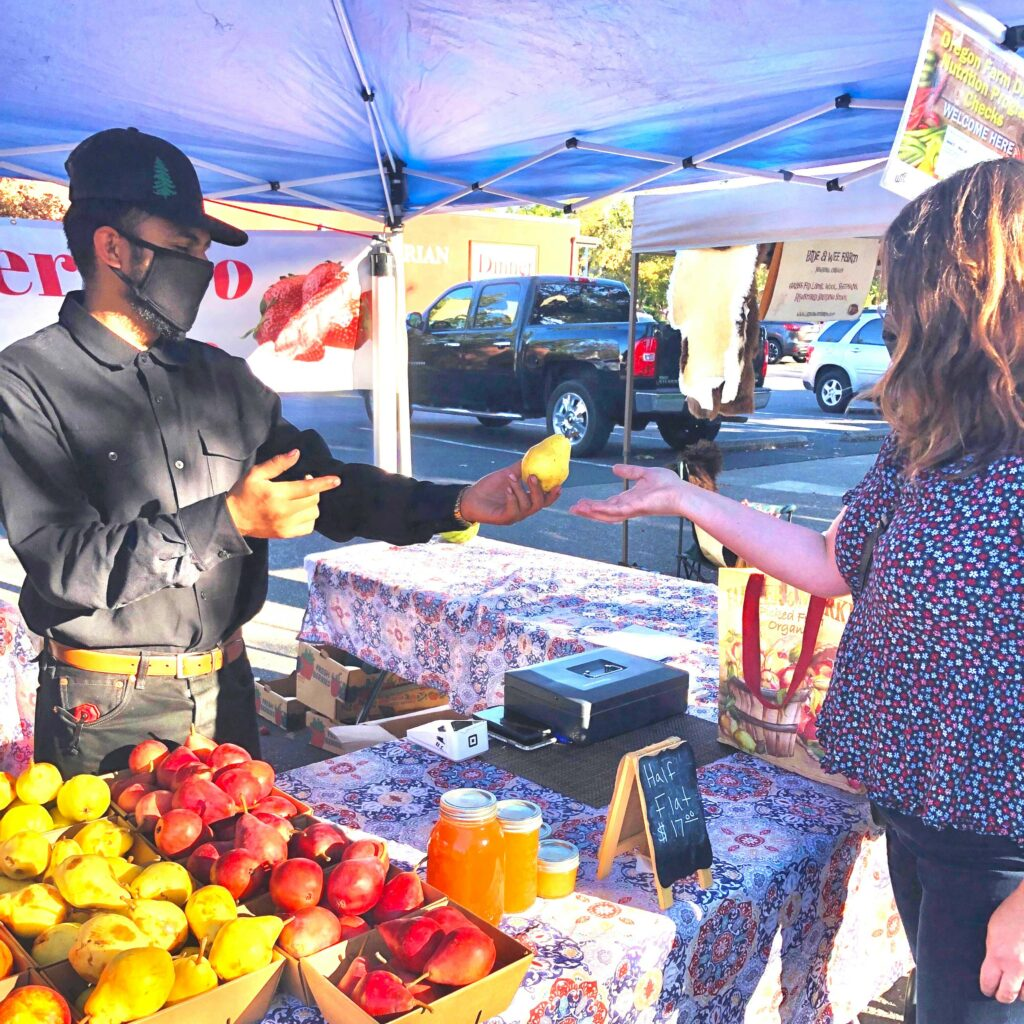 Farmer, Gustavo Guerrero hands Chef Rebecca a golden pear at his farmers market booth.