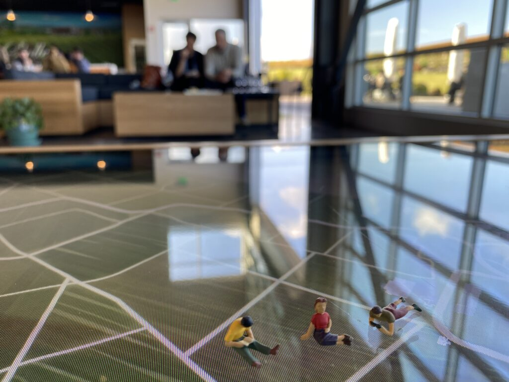 Three tiny travelers figurines sit on top of the interactive coffee table at the Stoller Experience Center.