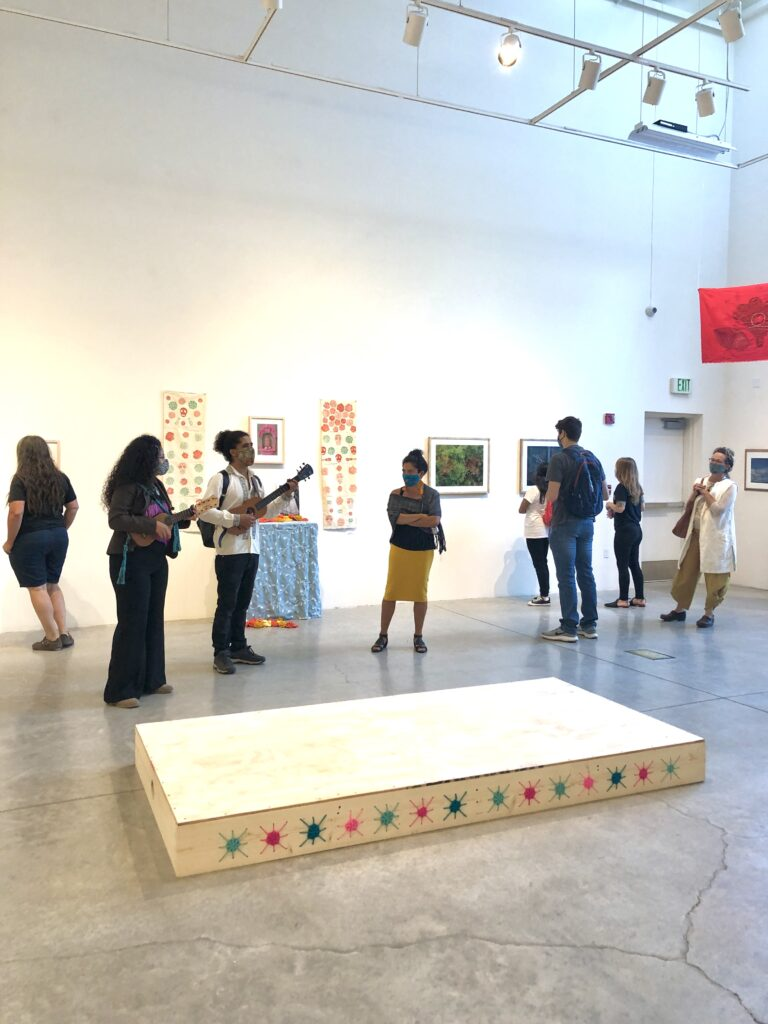 Musicians play in an art gallery, as patrons wander, chat, and view the art.