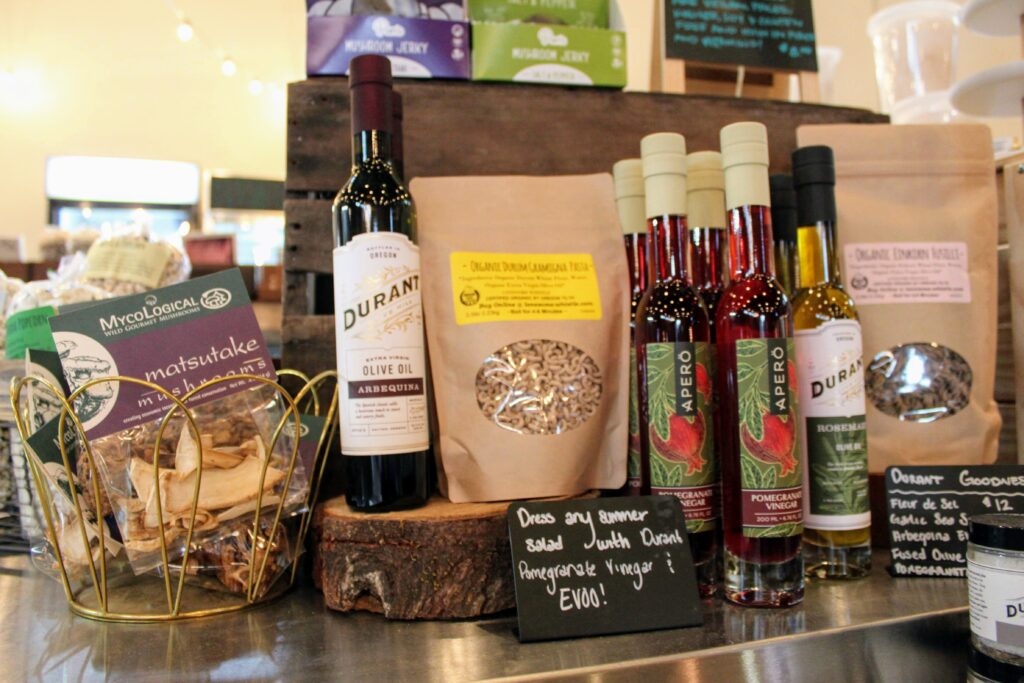 Dried matsutake mushrooms, Durant olive oils and pomegranate vinegars, and dried pasta are displayed on a shelf.