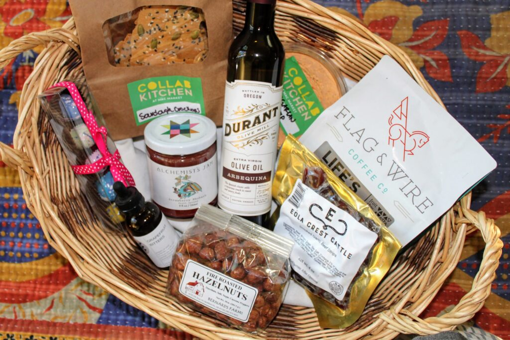A wicker basket is full with gift items such as sourdough crackers and hummus from Collab Kitchen, Flag & Wire Coffee, Durant Olive Oil, Eola Crest Cattle Jerky, Bernards Farm Fire Roasted Hazelnuts, Free Wild She Grapefruit Bitters, Suzy's Chocolates, and Alchemist's Jam.