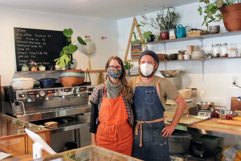 Jennifer and Danny, owners of Alchemist's Jam stand in front of their store counter.