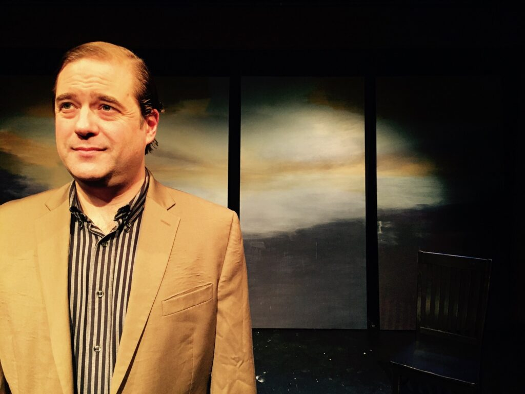 The actor, Lance Nuttman stands in the glow of theater lights with a simple set behind him.