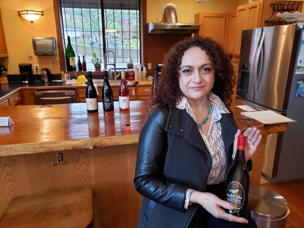 Tasting room associate, Monica Macias of Yamhill Valley Vineyards stands in front of a counter with wine bottles displayed on it. She holds a bottle of wine.