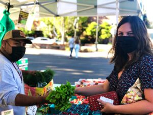 Chef Rebecca Clarke visits Pablo Munoz Farms' booth at the Downtown McMinnville Farmers Market.