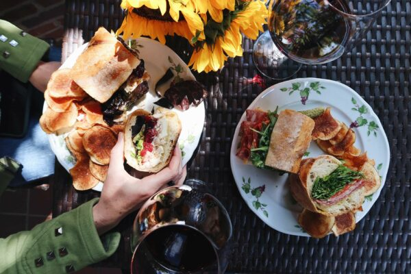 An outdoor table is set with two gourmet Italian sandwiches, chips, two glasses of wine, and a vase full of sunflowers.