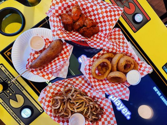 Hand dipped corndog, onion rings, hot wings and curly fries are set atop an arcade game.