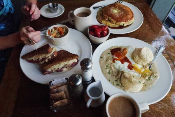 A table is set with biscuits and chicken gravy, a reuben, pancakes, and fruit.