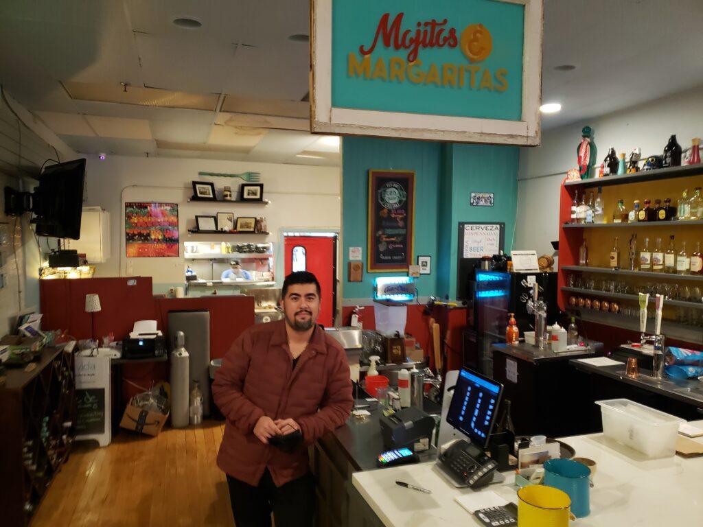 Pura Vida chef and owner, Ricardo Antúnez stands in front of the bar in his restaurant, Pura Vida Cocina.