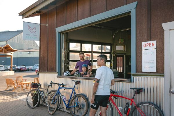 A group of cyclists take a break outside of Flag & Wire Coffee at their large open window.