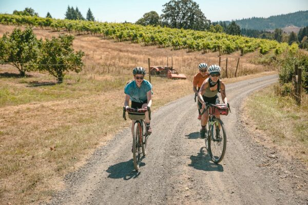 A group of cyclists ride on a gravel road with a vineyard in the background.
