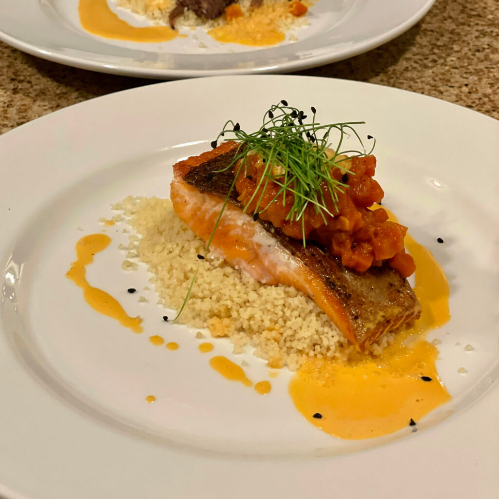 A plate with a salmon fillet served atop a bed of couscous.  Tomatoes and microgreens are on top of the salmon.