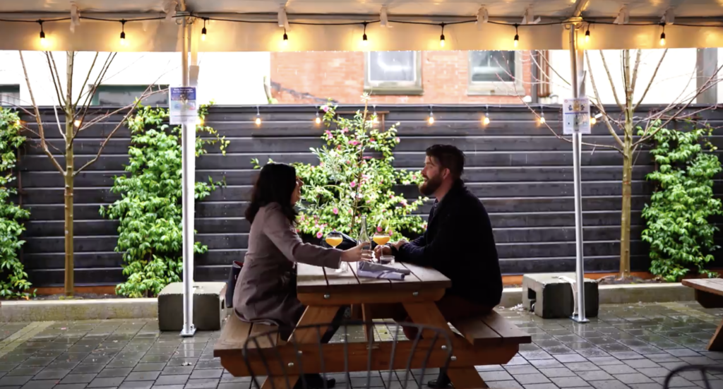 A man and woman sit at a picnic table beneath a dining tent. They appear to be talking, and each have a mimosa in front of them. Romantic lights hang from the top of the tent and blooming plants grow up a wall in the background.