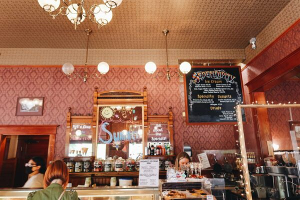The inside of Serendipity Ice Cream has some antique lights, a dusty pink wall and high ceilings. The ice cream menu is on the wall.