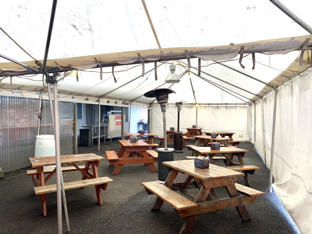 A large outdoor dining tent with sides.  There are heaters and several picnic tables nestled within.
