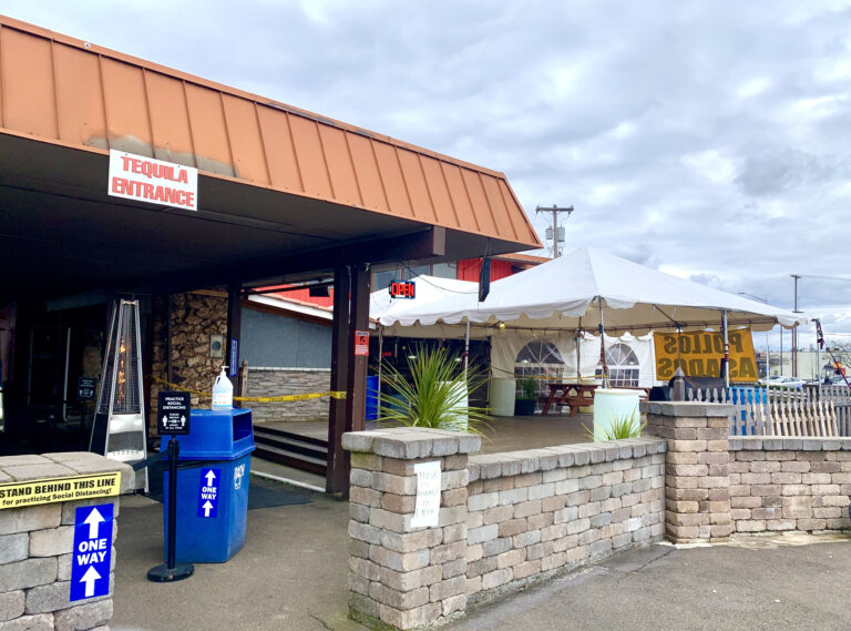 Outdoor entrance to Tequila grill. You can see signage requiring social distancing and mask requirements. In the background, you there's a large patio space with much tent cover.