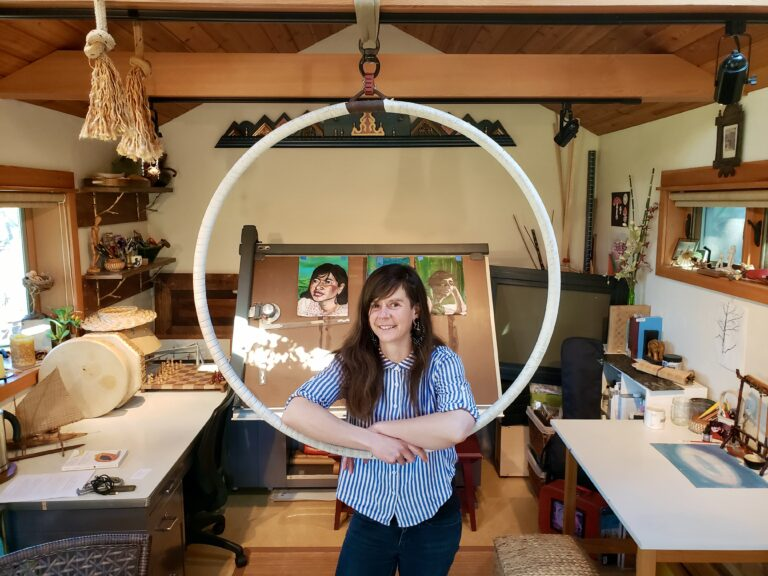 Thea Gahr poses in her art studio at the center of a hanging hoop.