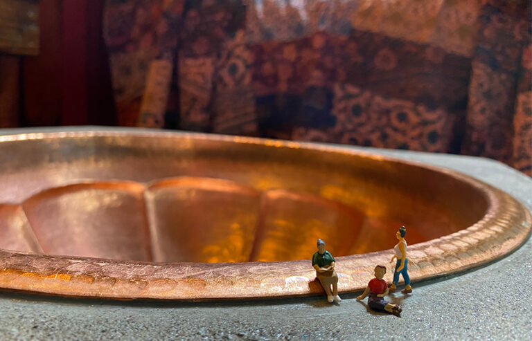 Three tiny people figurings are placed in front of a copper sink.