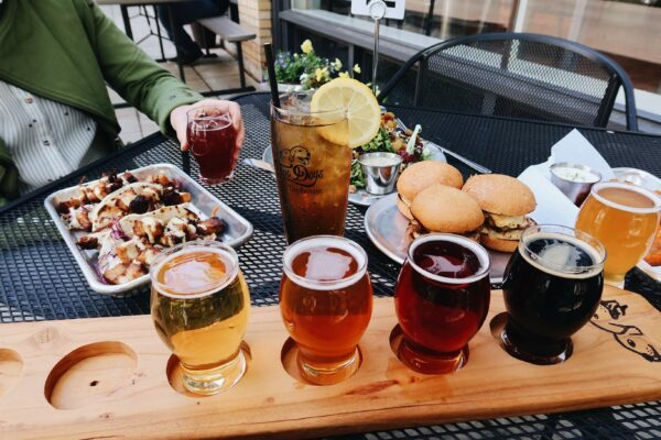 An outdoor table is set with a colorful flight of beer, tacos, sliders, and salad.