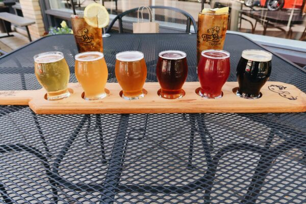A colorful beer flight is staged on an outdoor table with two glasses of iced tea with lemon.