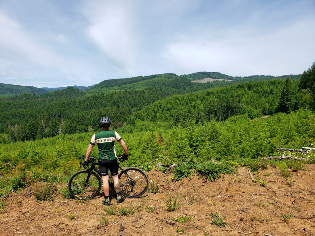 A man stands with his bike, overlooking a vast valley filled with evergreen trees