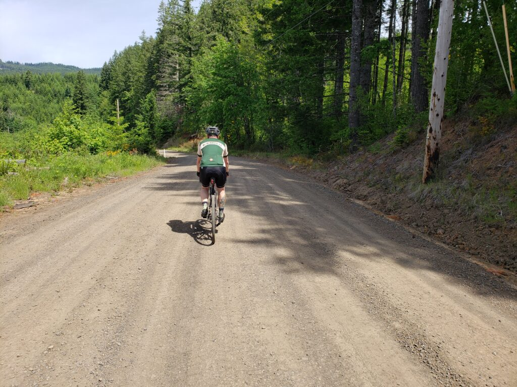 A man rides his bike on a gravel road.
