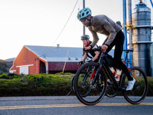 Two cyclists riding bikes in front of a barn