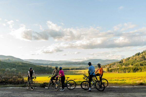 A group of cyclists take a break with a beautiful, sunny, valley view in the background.