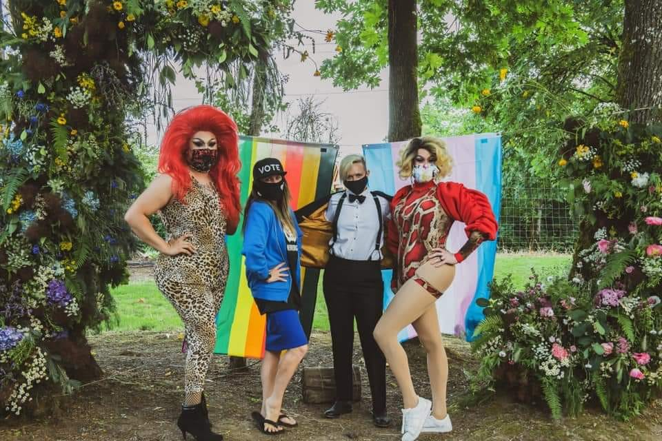 Wine Country Pride Organizers pose with drag queen performers in front of pride flags.